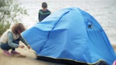 stan : Family of children and mothers gather a tourist tent on the bank of the river of the sea Dostupné videozáznamy