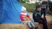 tenda : A beautiful girl with her family plays on a ukulele on the river bank near a tourist tent Stock Footage