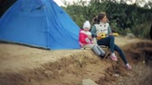 enstrüman : A beautiful girl with her family plays on a ukulele on the river bank near a tourist tent Stok Video