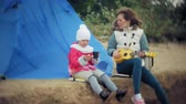 stan : A beautiful girl with her family plays on a ukulele on the river bank near a tourist tent Dostupné videozáznamy