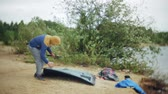 kids tent : Man collects a tourist tent on the bank of the river of the sea Stock Footage