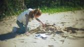 csontváz : The woman is engaged in excavating bones in the sand, Skeleton and archaeological tools. Stock mozgókép