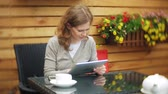 чай : Young woman uses a tablet and phone, drinks tea in a cafe bar Стоковые видеозаписи