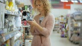 baby store : Young woman stands near the supermarket shelf and selects the products Stock Footage