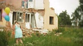 nukleáris : A little girl in a gas mask walks through the ruined buildings with balloons in her hand
