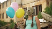 spacer : A little girl in a gas mask walks through the ruined buildings with balloons in her hand