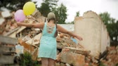 защита : A little girl in a gas mask walks through the ruined buildings with balloons in her hand