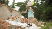 balloon : A little girl in a gas mask on the ruins of a building and holding on to a doll and balloons.