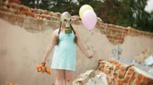 balony : A little girl in a gas mask on the ruins of a building and holding on to a doll and balloons.