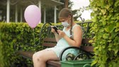 tosse : Cute girl in a respirator uses tablet in the park on a bench