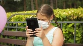 sevimli kız : Cute girl in a respirator uses tablet in the park on a bench