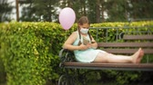 tosse : Cute girl in a respirator reading a book in the park on a bench