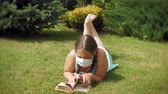 tosse : Cute girl in a respirator reading a book in the park Stock Footage