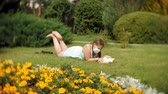 hastalık : Cute girl in a respirator reading a book in the park Stok Video