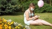 sevimli kız : Cute girl in a respirator reading a book in the park Stok Video