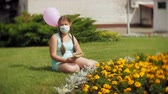 opieka : Cute girl in a respirator reading a book in the park Wideo