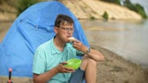 eklemek : A man is eating around a kettle in a campsite with a tent on the background. Stok Video