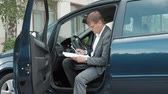 discagem : Mature businessman in car holds documents and uses smartphone