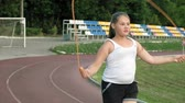 colega : Little fat girl jumping rope in the stadium Vídeos