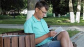 образованный : A man in glasses sits on a bench in the park and reads a book