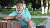 city lifestyle : A man in glasses sits on a bench in the park and uses a phone Stock Footage