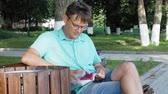 eğitim : A man in glasses sits on a bench in the park and uses a phone Stok Video