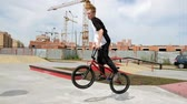 menino : A boy is riding BMX cycling tricks in a skateboard park on a sunny day. Super Slow Motion Stock Footage
