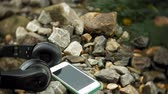 earbuds : headphones and a smartphone lying on rocks near the sea, beating waves