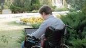 гандикап : A disabled man is sitting in a wheelchair and working on a laptop in the park