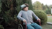 blind : A disabled man in a wheelchair chair dresses a virtual reality helmet