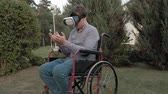 paraplegic : A disabled man in a wheelchair chair uses a virtual reality helmet Stock Footage