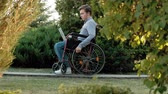 инвалид : A disabled man is sitting in a wheelchair and working on a laptop in the park