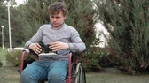 paraplegic : A disabled man in a wheelchair chair removes the virtual reality helmet Stock Footage