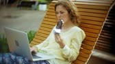 analiz etmek : Beautiful woman eats an ice cream and works on a laptop on a wooden bench in the park