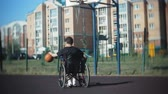 инвалид : Disabled man plays basketball from his wheelchair, On open air