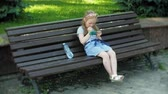 ławka : Little girl sitting on a wooden bench in the city uses a smartphone, urban park background