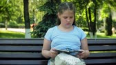 casual sitting : Young girl sitting on a wooden bench in a city reading a book, background of a city park Stock Footage