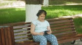 教育 : Little fat girl with a tablet PC and headphones sitting on a bench listening to music or watching a video in a summer park