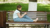 educação : Little fat girl with a tablet PC and headphones sitting on a bench listening to music or watching a video in a summer park