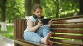 naslouchání : Little fat girl with a tablet PC and headphones sitting on a bench listening to music or watching a video in a summer park