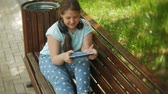 studenci : Little fat girl with a tablet PC and headphones sitting on a bench listening to music or watching a video in a summer park