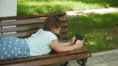 tabletler : Little fat girl with a tablet PC and headphones sitting on a bench listening to music or watching a video in a summer park