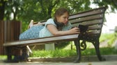 životní styl : Little fat girl with a tablet PC and headphones sitting on a bench listening to music or watching a video in a summer park