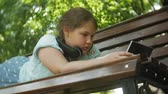 computador tablet : Little fat girl with a tablet PC and headphones sitting on a bench listening to music or watching a video in a summer park