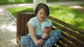 comprimido : Little fat girl with a tablet PC and headphones sitting on a bench listening to music or watching a video in a summer park