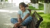 escuta : Little fat girl with a tablet PC and headphones sitting on a bench listening to music or watching a video in a summer park