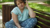 tablet pc : Little fat girl with a tablet PC and headphones sitting on a bench listening to music or watching a video in a summer park