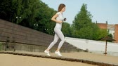 maraton : Young fitness woman engaged in bek outdoors, wearing headphones. Super slow motion