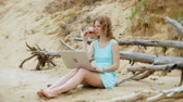 co işçi : busy beautiful young woman working on a laptop computer with business papers picking up a phone to work a call sitting on the beach by the sea on a sunny day and drinking wine from a glass