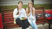 çiğneme : Two little girls, slim and fat, eat healthy and harmful food, vegetables and cakes sitting on a bench in a cafe, the concept of a healthy diet...
